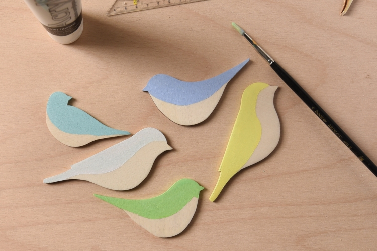 Colorful wooden birds in yellow, green, light blue and turquoise